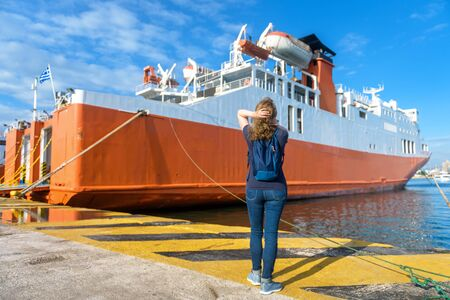 Young woman looks at ferryboat in seaport of Piraeus, near Athens, Greece. Large ship docked in sea harbor in summer. Car-ferry loading or unloading at a port pier. Concept of transport and travel.