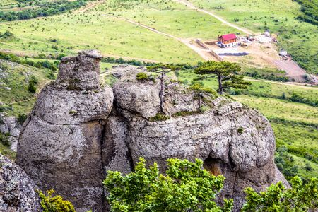 Mountain landscape of Crimea, Russia. Scenic view of rocks on Demerdji mountain and house. Valley of Ghost is a tourist attraction of Crimea. Beautiful nature of Southern coast of Crimea in summer.