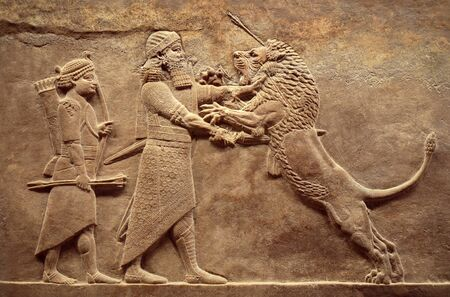 Assyrian wall relief, detail of panorama with royal lion hunt. Old carving from the Middle East history. Remains of culture of Mesopotamia ancient civilization. Amazing Babylonian and Sumerian art. Stock Photo