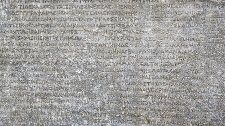 Ancient Greek writing on rock for background. Antique inscription carved on stone. Old script text close-up. Gray wall with historic letters. Vintage texture with words from past civilization. 免版税图像 - 131671312