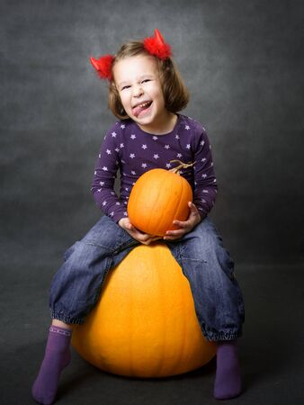 Halloween concept. Little girl with costume horns having fun. Adorable child sits on pumpkin and grimaces. Toddler smiles and shows tongue. Studio portrait of cheerful kid on Halloween.