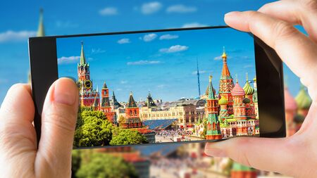 Moscow Kremlin and St Basils Cathedral in summer, Moscow, Russia. Tourist taking photo of old Moscow by mobile phone. Sunny picture of the heart of Moscow on smartphone. Travel and vacation concept.