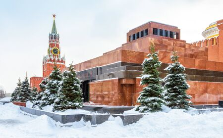 Moscow Red Square in winter, Russia. Lenin's Mausoleum by Moscow Kremlin under snow. This place is a famous tourist attraction of Moscow. The inscription is Lenin. Center of Moscow during snowfall. 免版税图像