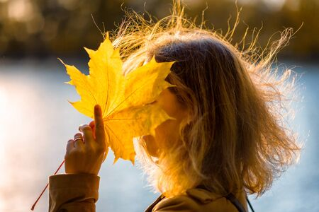Autumn maple leaf in hand of woman outside. Scenery of autumn park on sunny day. Woman closes her face with yellow leaf in autumn forest at sunset. Beautiful fall nature. Autumn season concept. Foto de archivo - 131363027