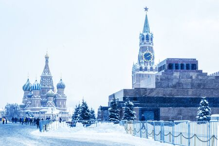 Moscow Red Square in winter, Russia. This place is a famous tourist attraction of Moscow. Cold winter view of St Basil Cathedral and Moscow Kremlin. Panorama of Moscow city center during snowfall.
