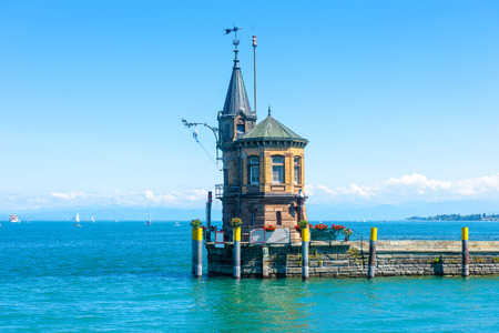 Lighthouse on old pier in harbor of Constance or Konstanz, Germany. Beautiful scenic view of Constance Lake (Bodensee) in summer. Scenery of vintage lighthouse on background of blue water and sky.