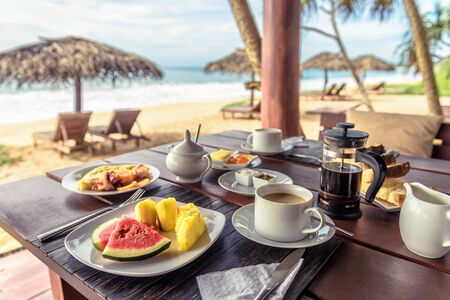 Breakfast on sea beach in Sri Lanka. Table setting with vegan food and coffee in restaurant outdoor. Buffet with exotic fruits on ocean coast. Concept of travel and vacation in tropical resort. Stock Photo
