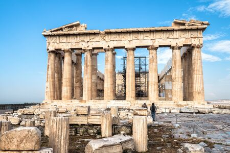 Parthenon on Acropolis hill, Athens, Greece. It is a top landmark of Athens. Ancient Greek ruins in Athens center in summer. Tourists look at the famous temple, remains of classical Athenian culture.