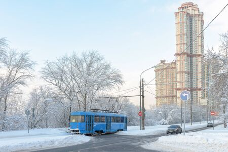 Moscow after snowfall in winter, Russia. Tram goes on street covered snow. Cold and frost in Moscow. Panoramic view of snowy city. Urban transport run on frozen road.