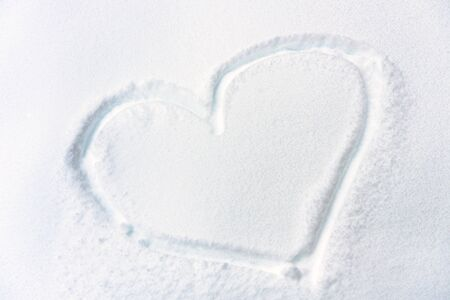 Heart drawn on fresh snow texture. Symbol of heart on snowy surface closeup. Concept of love, romance and winter holiday. Heart shape on white pure background in nature. Stock fotó