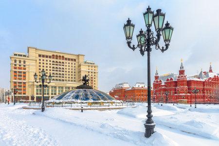 Mosca, Russia - 5 febbraio 2018: Piazza Manezhnaya sotto la neve a Mosca. Bella vista panoramica del centro nevoso di Mosca nel gelido inverno. Cupola con statua di San Giorgio e Four Seasons Hotel dietro di essa.
