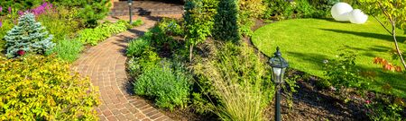 Landscaping in nice green garden in summer. Panoramic view of landscaped place at residential house. Paving path and vintage lantern in home backyard or yard. Scenery of beautiful landscape design.