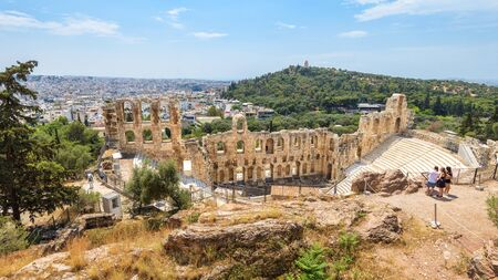 Odeon of Herodes Atticus at Acropolis of Athens, Greece. It is famous landmark of Athens. Panoramic scenic view of ancient theater overlooking Athens city. Nice landscape with classical Greek ruins.