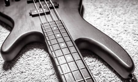 Bass guitar with four strings in black and white closeup. Detail of popular rock musical instrument. Close view of electric bass on carpet. Vintage style photo of wooden textured guitar neck.