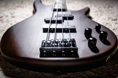 Bass electric guitar with four strings closeup. Detail of popular rock musical instrument. Close view of bass, focus on bridge. Vintage style photo of wooden bass guitar body. Stock Photo