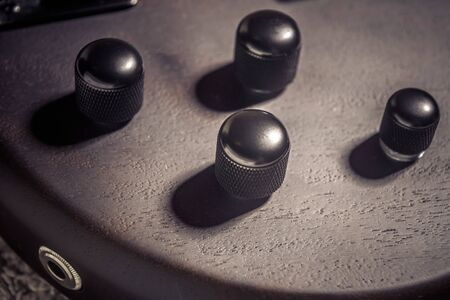 Bass electric guitar with four strings closeup. Detail of popular rock musical instrument. Close view of elements of wooden textured bass. Macro vintage photo of control knobs of brown guitar. Stock Photo