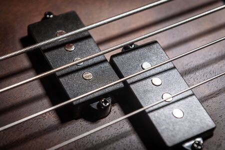 Bass electric guitar with four strings closeup. Detail of popular rock musical instrument. Close view of element of wooden textured bass. Macro photo of pickups of brown bass guitar.