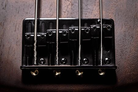 Bass electric guitar with four strings closeup. Detail of popular rock musical instrument. Close view of element of wooden textured bass. Macro photo of metal bridge of brown bass guitar. Stock Photo