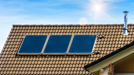 Solar panel on residential house rooftop. Solar system on roof of home close-up. Blue solar cells on building top for alternative energy. Photovoltaic eco panels for electricity from clean sun power. Stock Photo