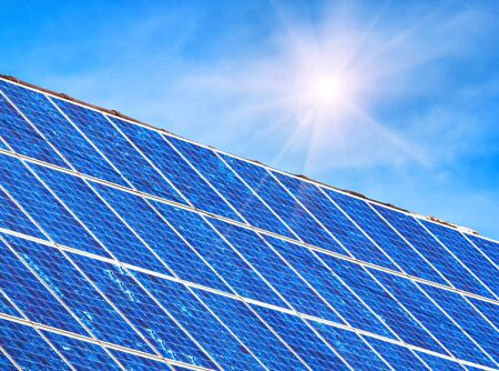 Solar panel on residential house rooftop. Many blue solar cells on building top for alternative energy. Photovoltaic eco panels for electricity from clean sun power. Solar system on home roof closeup.