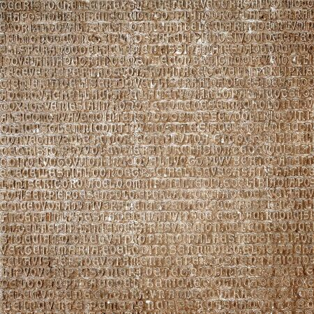 Ancient Latin writing background. Antique inscription carved on stone wall. Old classic script text close-up. Grunge surface with historic letters. Vintage texture with words from past civilization.