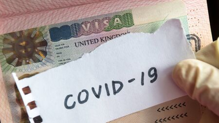 Coronavirus concept. Note COVID-19 coronavirus and UK visa in passport. Border control and quarantine of tourists infected with coronavirus.