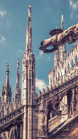 Milan Cathedral roof close-up, Italy, Europe. Milan Cathedral or Duomo di Milano is top landmark of Milan city. Luxury decorations detail of Milan architecture. Vintage style photo of Gothic rooftop. Stock Photo