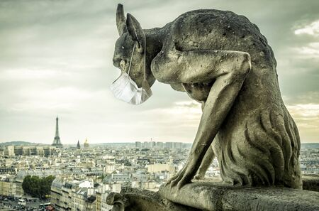 COVID-19 coronavirus in France, medical mask on gargoyle of Notre Dame in Paris. Tourist landmarks closed due to corona virus outbreak. Concept of travel, quarantine and COVID coronavirus pandemic. Banque d'images