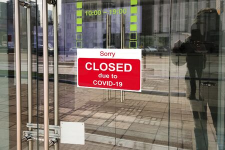 Business center closed due to COVID-19, sign with sorry in door window. Stores, restaurants, offices, other public places temporarily closed during coronavirus pandemic. Economy hit by corona virus. Banque d'images