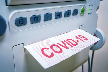COVID-19 coronavirus concept, medical equipment for diagnostics in hospital or clinic, machine and paper with inscription COVID. Treatment and care during COVID19 pandemic and corona virus outbreak.