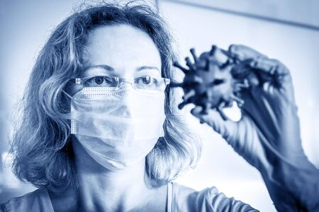 Researcher looks at coronavirus in her hand, focus on eyes, COVID-19, science virology and technology concept, medical research during COVID pandemic. Development of vaccine due to corona virus.