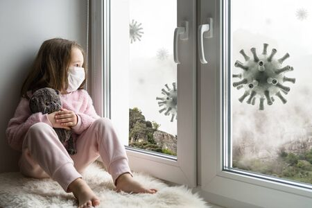 Coronavirus and quarantine concept, sad kid in medical mask looks out window, little girl sits on windowsill safe from corona virus during COVID-19 pandemic. People stay at home due to coronavirus. Banque d'images