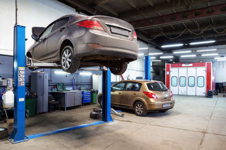 Moscow, Russia - March 19, 2020: Interior of auto repair workshop, car on lift in mechanic shop or garage, vehicles inside maintenance. Small service station during COVID-19 coronavirus pandemic.