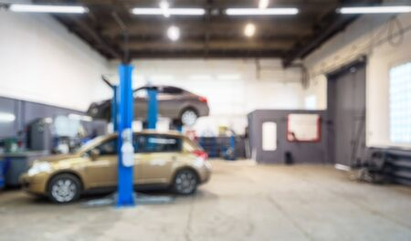 Car repair shop interior in bokeh, blurred defocused background. Auto on lift in mechanic workshop or garage, vehicles inside maintenance. Workplace and business - small service station. Banque d'images