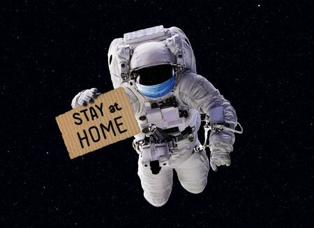 COVID-19 coronavirus quarantine concept, funny astronaut wearing medical mask in outer space  slogan Stay at Home on cardboard during corona virus pandemic.      . Banque d'images