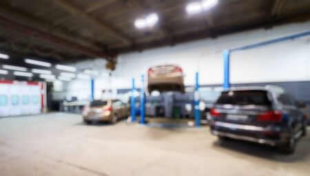 Auto repair workshop interior in bokeh, blurred defocused background. Car on lift in mechanic shop or garage, vehicles inside maintenance, workplace and business - small service station.