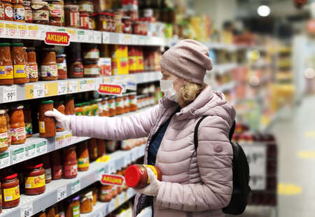 Moscow – May 17, 2020: Coronavirus and retail concept, woman wearing medical mask looks at grocery in supermarket. Consumer in face mask shopping food in store during COVID-19 corona virus pandemic. Éditoriale