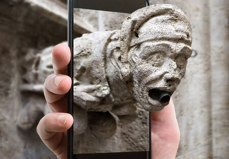 Gargoyle on Marienplatz, Munich, Bavaria, Germany. Picture of detail of Munich landmark on smartphone screen, funny photo of Gothic gargoyle and mobile or cell phone. Concept of travel and technology. Stock Photo