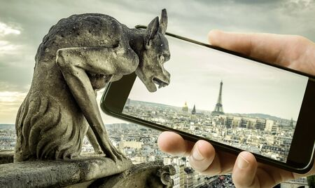 Gargoyle on Cathedral of Notre Dame de Paris looks at Eiffel Tower in mobile or cell phone, Paris, France. Funny photo of old Paris and smartphone. Concept of travel, adventure and technology. Stock Photo