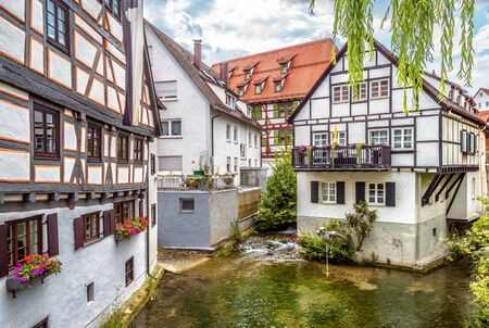 Street with vintage half-timbered houses in old town of Ulm, Germany. Medieval Fish Quarter is tourist attraction of Ulm. View of ancient Fisherman`s district of Ulm city and water canal in summer.