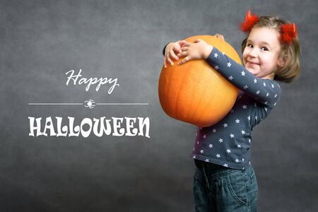Happy Halloween! Funny little girl holds big pumpkin and smiles. Adorable child and Halloween typography. Cute toddler with costume horns having fun. Studio portrait of cheerful kid on Halloween.