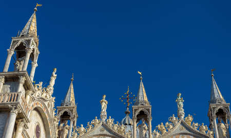 St Mark`s Basilica or San Marco, detail of facade top on blue sky background, Venice, Italy. Famous St Mark`s cathedral is main landmark in Venice. Beautiful ornate rooftop of medieval Gothic church.