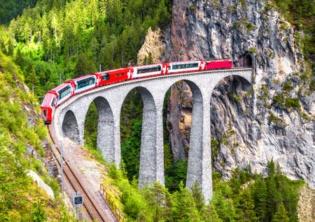 Landwasser Viaduct in Filisur, Switzerland. It is landmark of Swiss Alps. Bernina Express train on railroad bridge in mountains. Aerial scenic view of famous railway. Nice Alpine landscape in summer.
