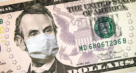Coronavirus in USA, President Lincoln with face mask on 5 dollar money bill. COVID-19 affects global stock market, economy hit by corona virus pandemic fears. Concept of crisis, recession and finance.
