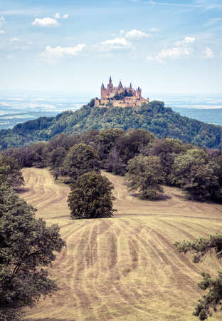 Hohenzollern Castle or Burg atop mount in summer, Germany. Famous old Gothic castle is landmark in Baden-Wurttemberg. Scenic view of fairytale German castle like palace in Swabia countryside. Editorial