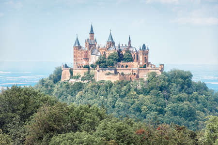 Hohenzollern Castle in summer morning, Germany. It is famous landmark in Stuttgart vicinity. Landscape with fairytale Gothic castle like palace. Scenic view of old German castle at misty mountain top. Editorial