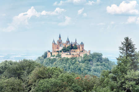 Landscape of misty mountain with Gothic Hohenzollern Castle in summer morning, Germany. Old Burg Hohenzollern is landmark in Stuttgart vicinity. Scenic view of fairytale German castle like palace.