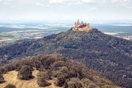 Hohenzollern Castle or Burg atop mount in summer, Germany. It is landmark in Baden-Wurttemberg. Landscape with fairytale Gothic castle, scenic view of old German castle like palace in countryside. Editorial