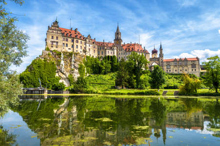 Sigmaringen Castle rising above Danube river, Germany. This beautiful castle is a landmark of Baden-Wurttemberg. Panorama of Swabian castle on a cliff. Scenic view of old German castle in summer.