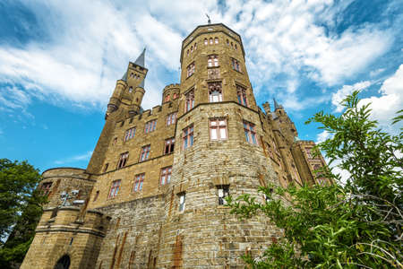 Hohenzollern Castle close-up, Germany. This castle is a landmark in Stuttgart vicinity. Bottom view of strong majestic Hohenzollern towers in summer. Famous Gothic castle in Swabian Alps.